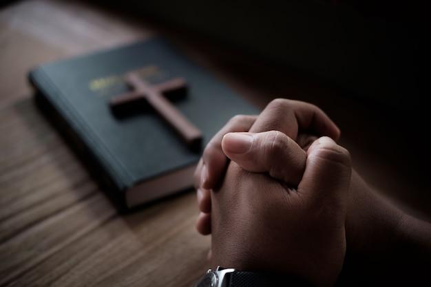 성경 기도하는 남자, 나무 탁자에 있는 그녀의 성경에 손을 깍지 끼고 있습니다.