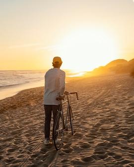 해변 전체 샷에서 자전거를 가진 남자