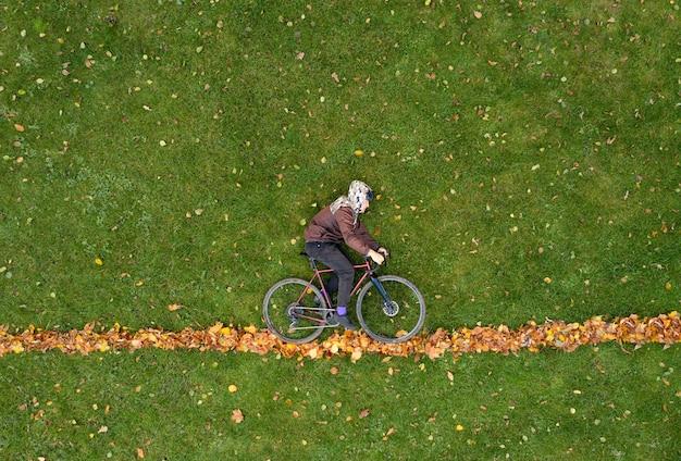 自転車を持った男は、紅葉の緑の草の上に横たわっています。クリエイティブなトレンディな秋のコンセプト。