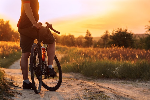日没時にフィールドのほこりっぽいトレイルに立っている自転車を持つ男。サイクリングのコンセプト。