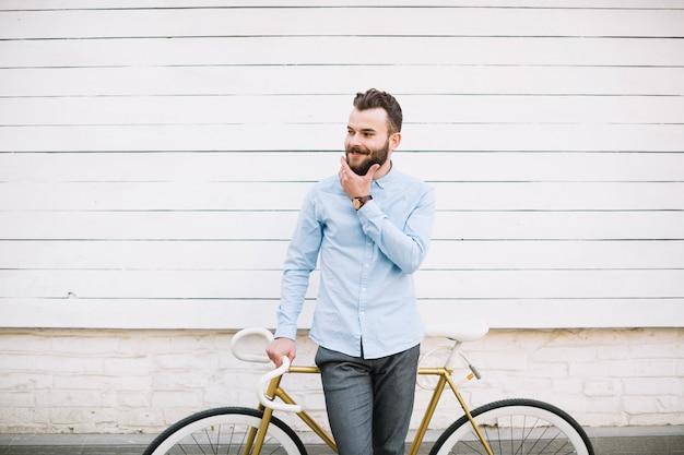 ひげに触れる自転車を持つ男
