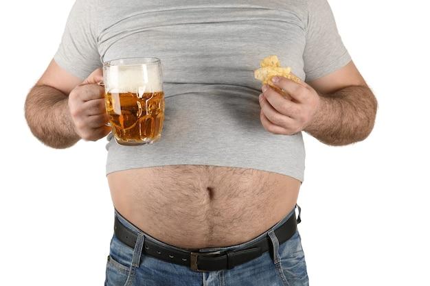Человек с большим животом, держащий стакан пива и закуски на белом фоне