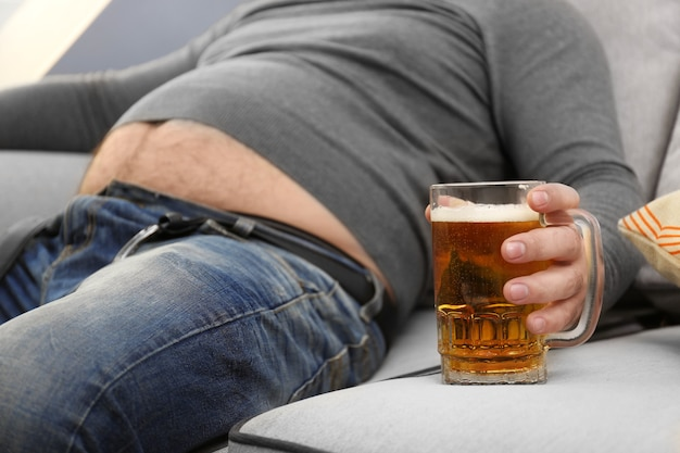 家でビールのガラスを保持している大きな腹を持つ男