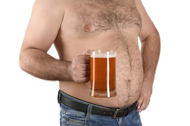 白い背景の上のビールのガラスを保持している大きな腹を持つ男