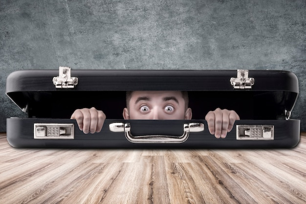 A man with big eyes looks out of a black case, the subject in the middle of the room Premium Photo