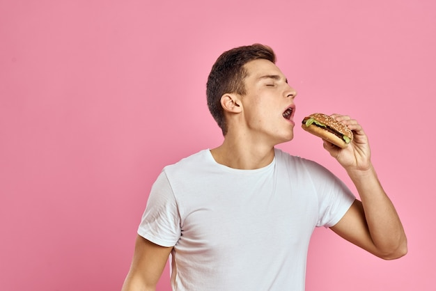 Man with big hamburger on pink background calories fast food cropped view copy space close-up. high quality photo