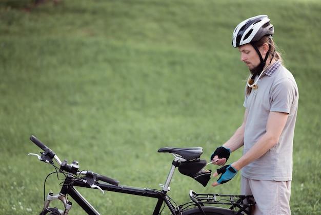 Человек с поломкой велосипеда ремонтирует свой велосипед на улице
