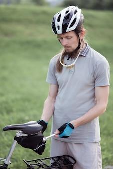自転車が故障した男が路上で自転車を修理する