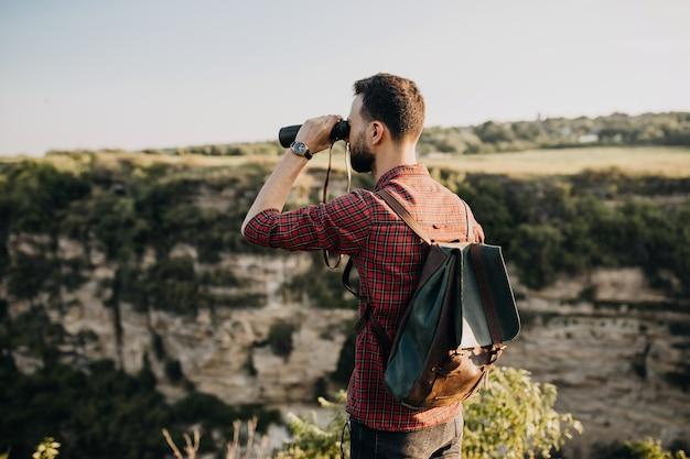 Человек с биноклем и рюкзаком, стоящий на скале в горах.