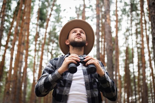 숲에서 쌍안경을 가진 남자입니다. 산이나 숲에서 하이킹.
