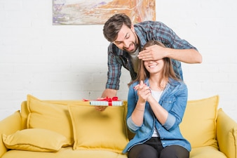 Man with birthday gift covering his girlfriend's eyes