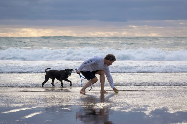 Man with black dog on piha beach