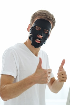 黒い顔のマスク、木炭を浄化する肌を持つ男。美容コンセプト