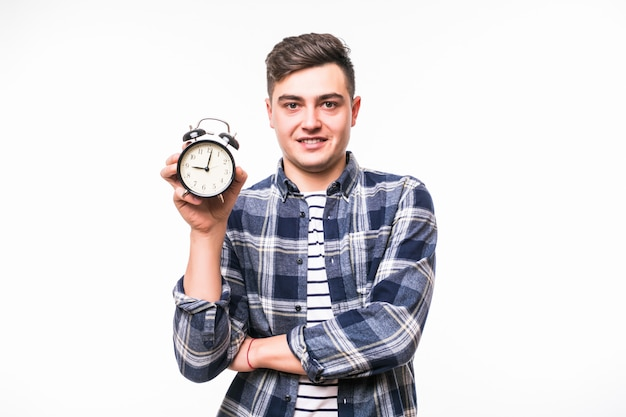 Man with black hair holds red alarm-clock dressed in casual clothes