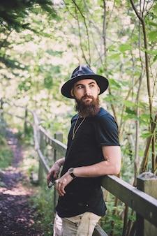 Человек с черной шляпой возле растений