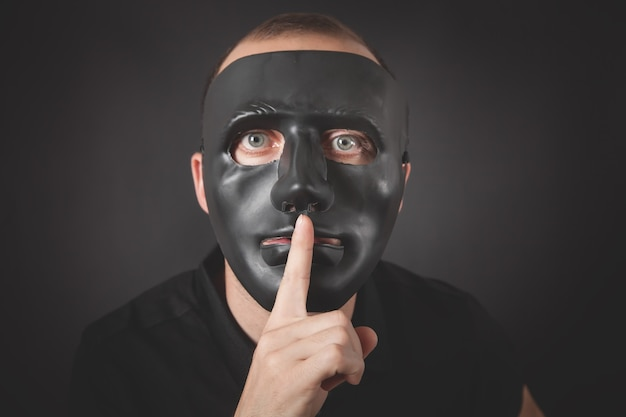 Man with a black mask making silence gesture. fake, anonymous