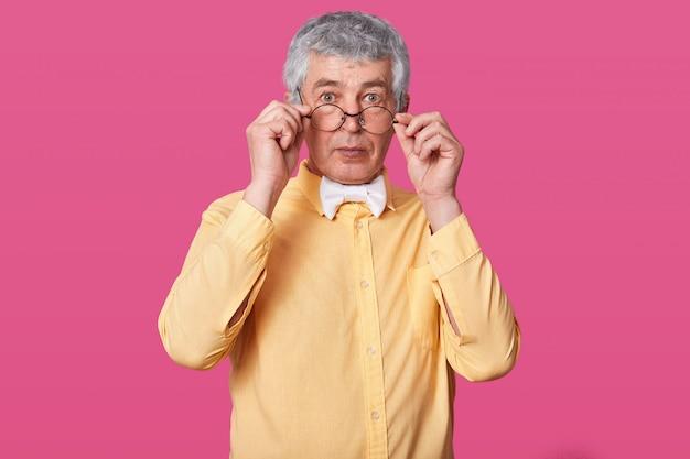 Uomo con gli occhiali neri arrotondati sulla punta del naso.