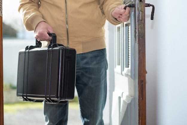 Man with a black suitcase going home