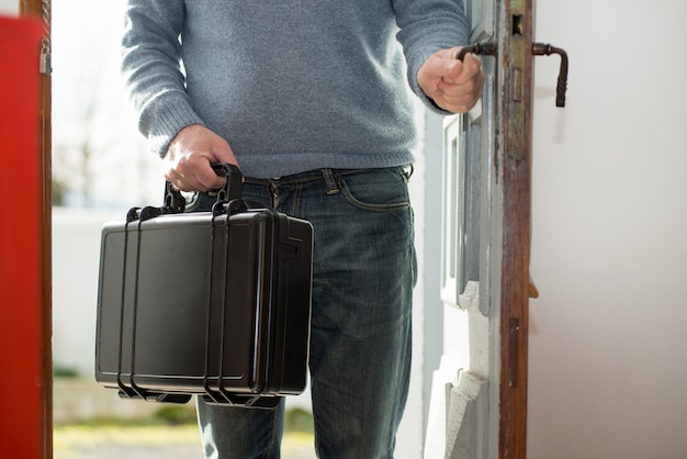 Man with black suitcase going home