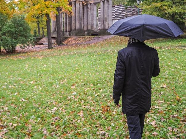 Человек с черным зонтиком в парке.