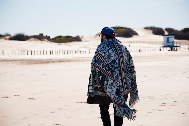 Uomo con una coperta che cammina sulla spiaggia
