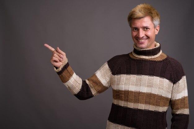 회색 벽에 고립 된 터틀넥 스웨터를 입고 금발 머리를 가진 남자