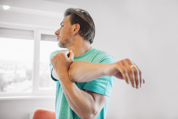 Man with blonde hair and bristle warming up before doing yoga at home