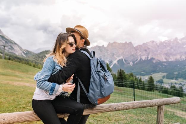 彼のガールフレンドを抱きしめ、素晴らしい山の風景を楽しんでいるエレガントな帽子をかぶった青いバックパックを持つ男