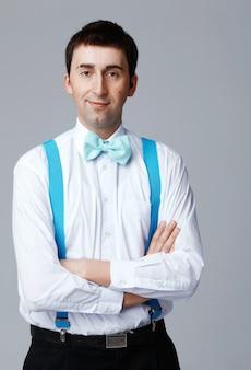 Человек с синим галстуком-бабочкой и латами, стоя со скрещенными руками.
