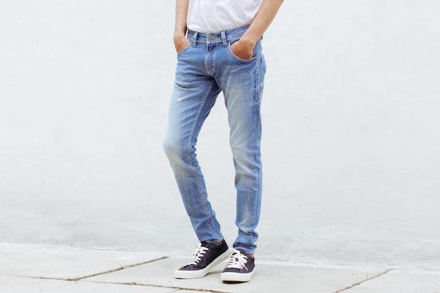青いデニムのズボンとスニーカーが立っている男
