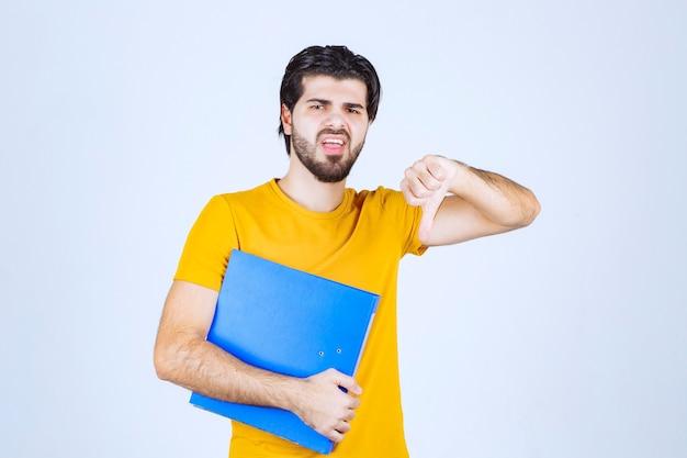 親指を下にやっている青いフォルダーを持つ男。