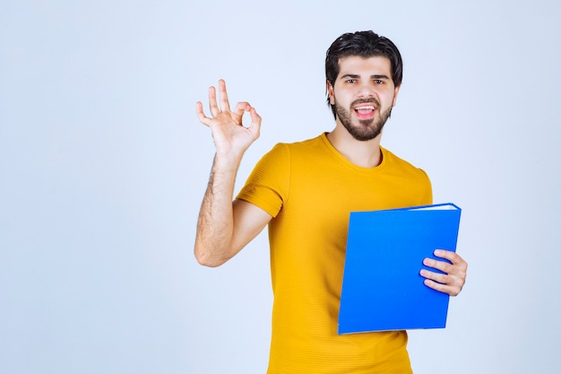 Man with blue folder giving friendly and peaceful poses.