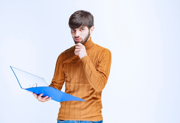 Man with a blue folder looks confused and terrified.