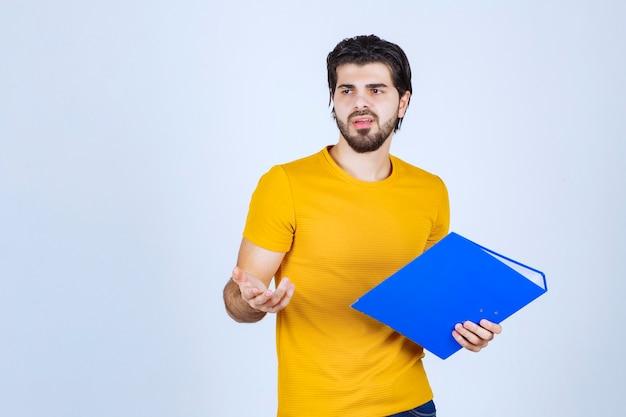L'uomo con una cartella blu sembra confuso o inesperto.