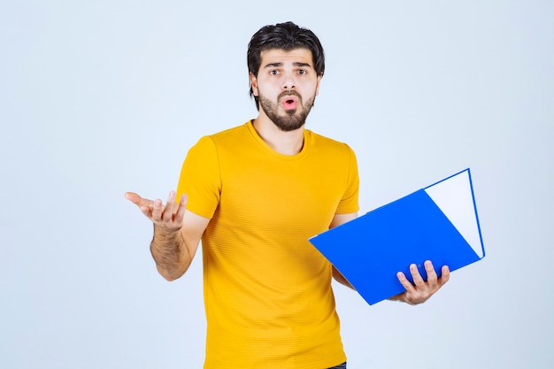 Man with a blue folder looks confused or unexperienced.