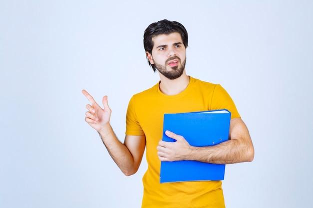 Uomo con una cartella blu che indica il suo collega sul lato sinistro e parla con emozioni.