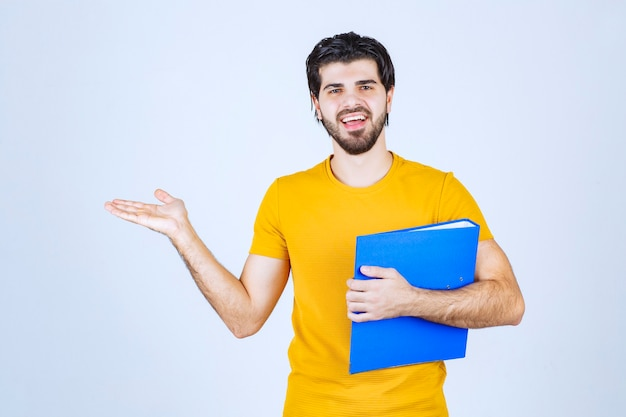 Man with a blue folder pointing his collegue on the left side and talking with emotions.