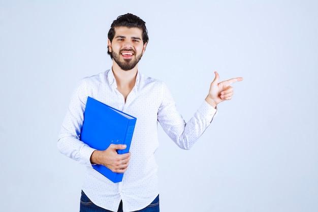 Uomo con una cartella blu che punta a destra Foto Gratuite