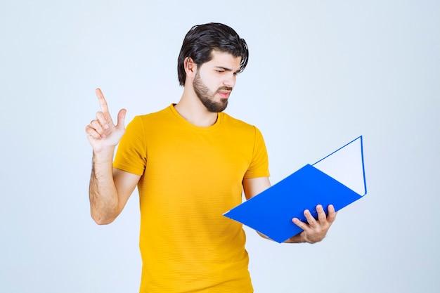 逆さまを指している青いフォルダーを持つ男。