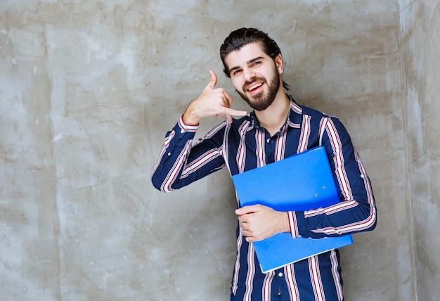 Uomo con una cartella blu che mostra il segnale di chiamata.