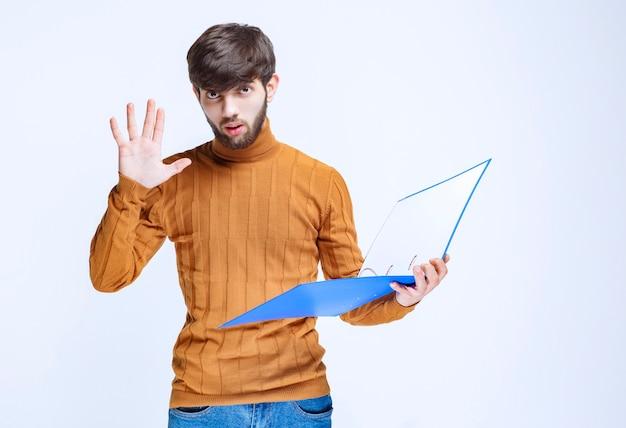 Uomo con una cartella blu che ferma qualcosa.