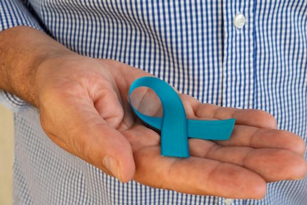 彼の手に青いリボンを持つ男。青い11月。前立腺がん予防月間。男性の健康。