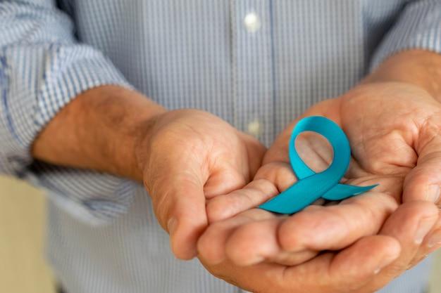 그의 손바닥에 블루 리본을 가진 남자입니다. 푸른 11월. 전립선암 예방의 달. 남자의 건강.