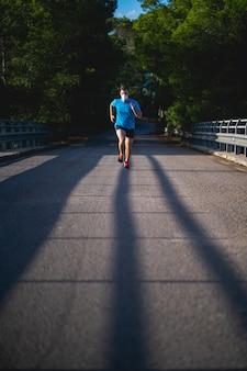 Человек с синей рубашкой и маской бежит по дороге в окружении природы