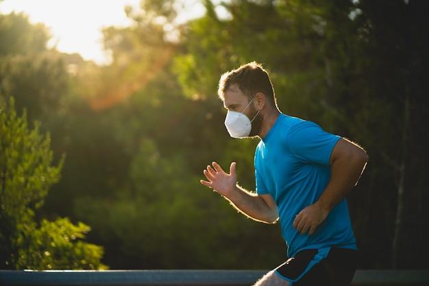 파란색 셔츠와 마스크가 자연에 둘러싸인 도로에서 실행되는 남자