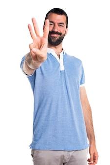 Uomo con camicia blu che conta tre