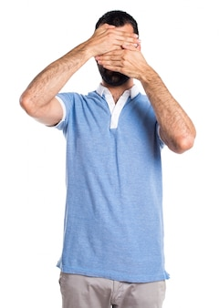 Man with blue shirt covering his face