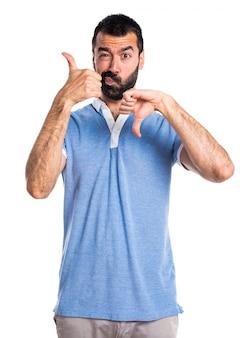 Man with blue shirt making good-bad sign