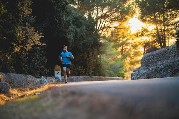 Человек в синей рубашке бежит по дороге в окружении природы во время заката