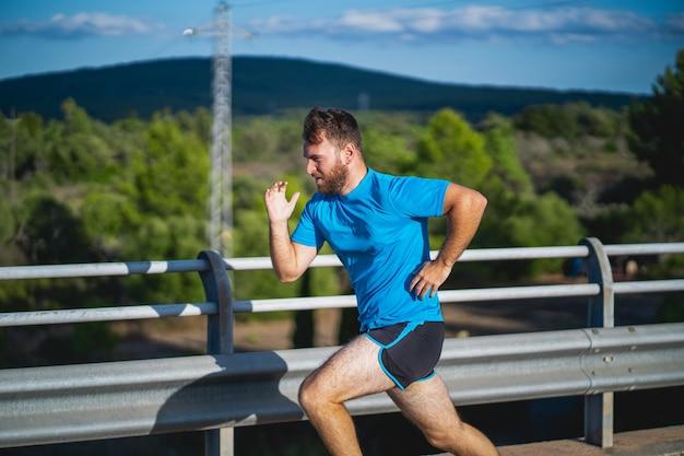 Человек с синей рубашкой бежит по дороге в окружении природы